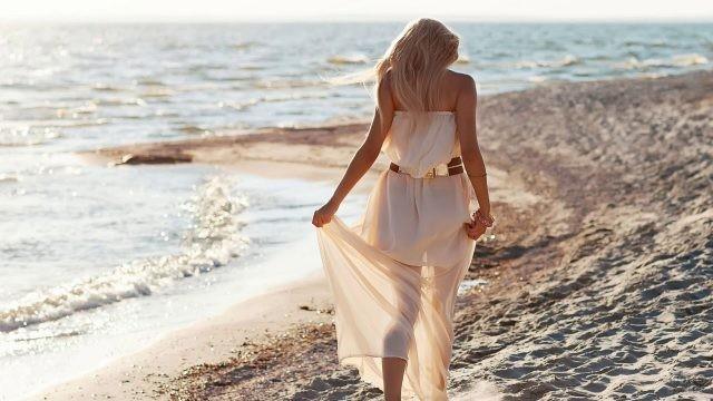 Девушка в белом платье идёт по песку
