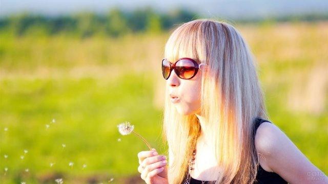 Девушка в солнечных очках дует на одуванчик