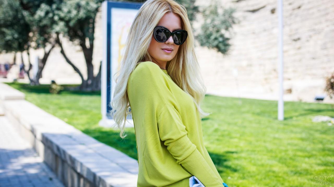 Девушка в зелёной кофточке в солнечных очках