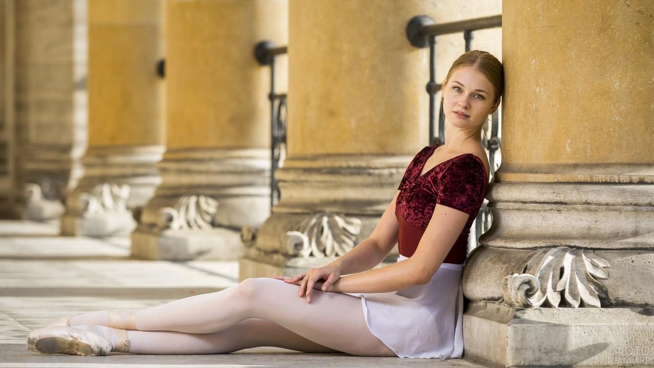 Балерина сидит у колонны