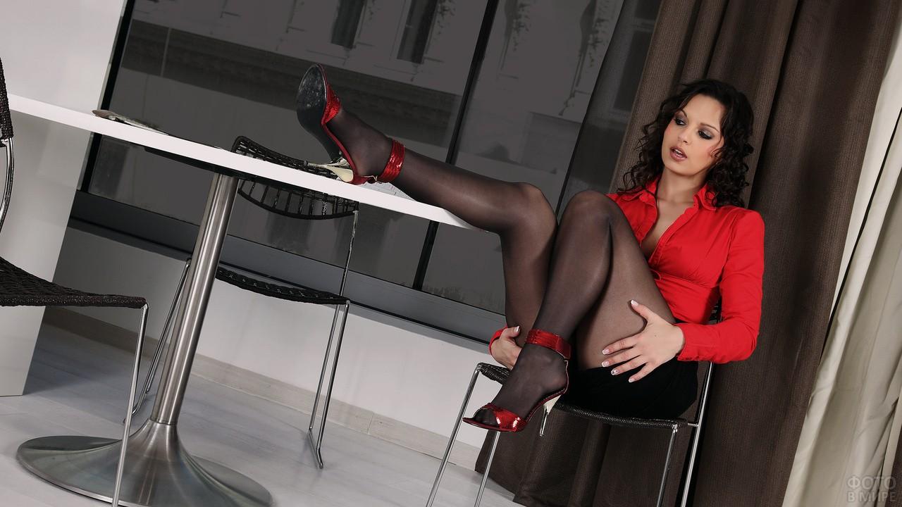 Брюнетка в красной блузке положила ногу на стол