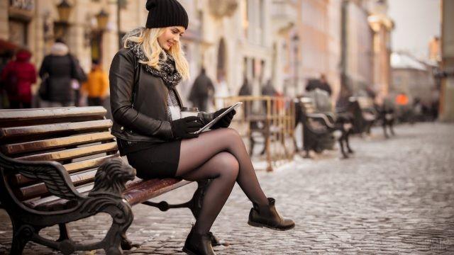 Девушка сидит на лавке с планшетом
