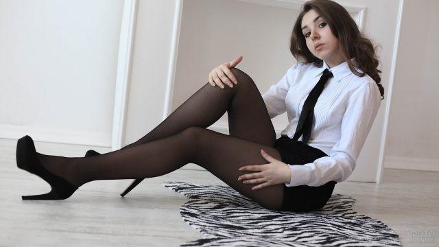 Девушка в белой блузке и юбке сидит на полу