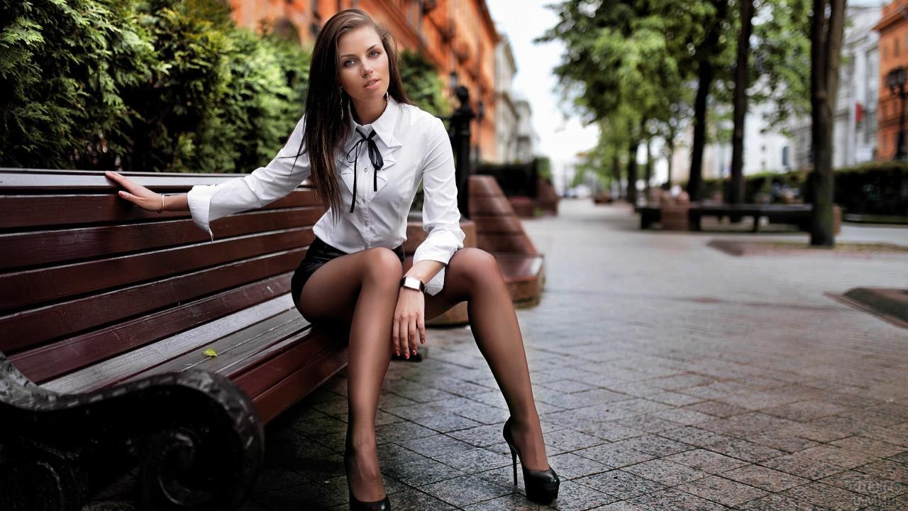 Девушка в городе сидит на скамейке