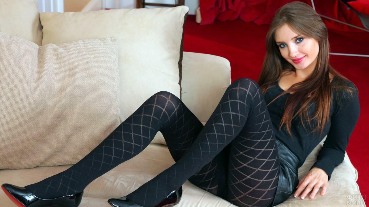 Девушка в колготках и туфлях на диване