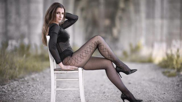 Девушка в колготках сидит на стуле