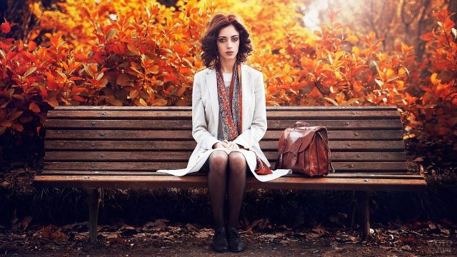 Девушка в парке сидит на скамейке