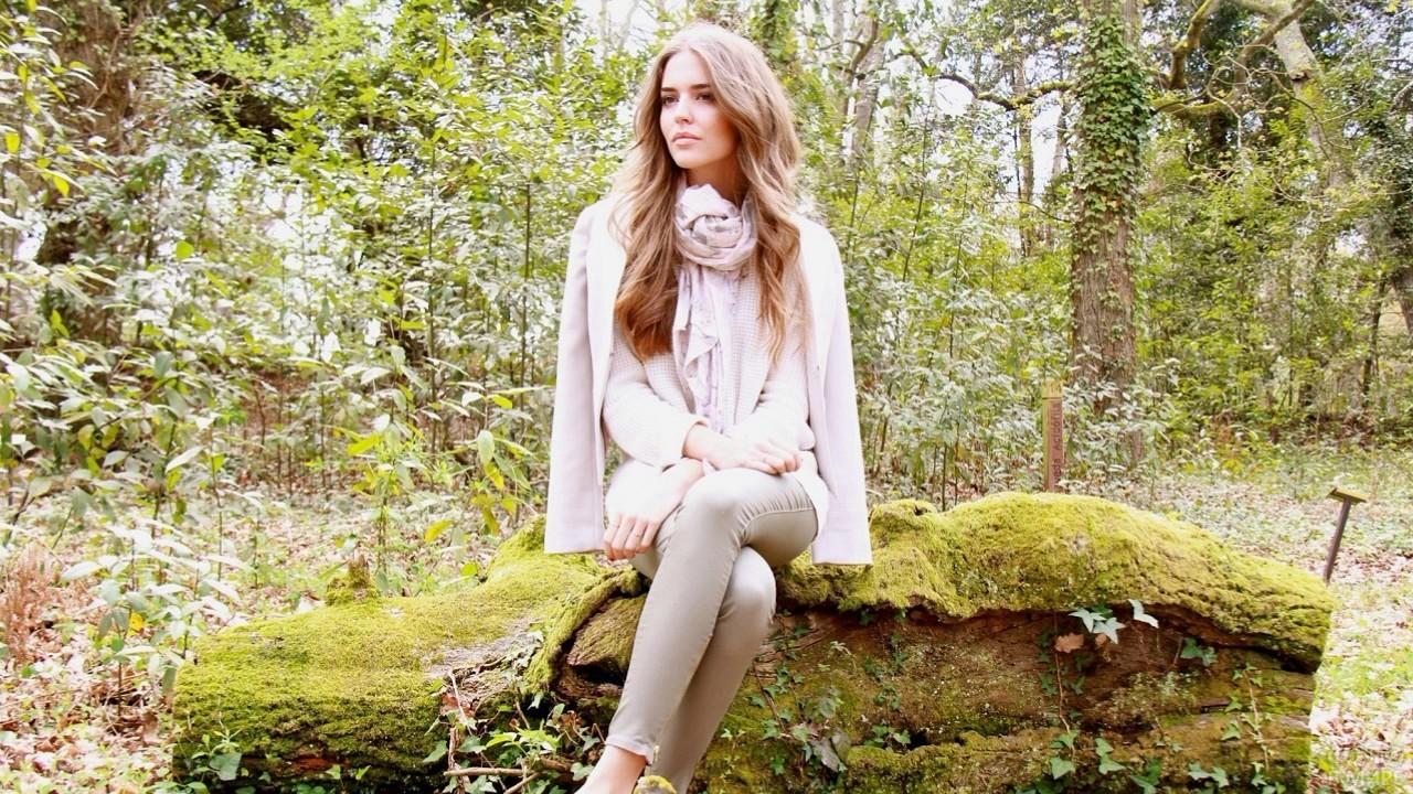 Девушка сидит на замшелом камне