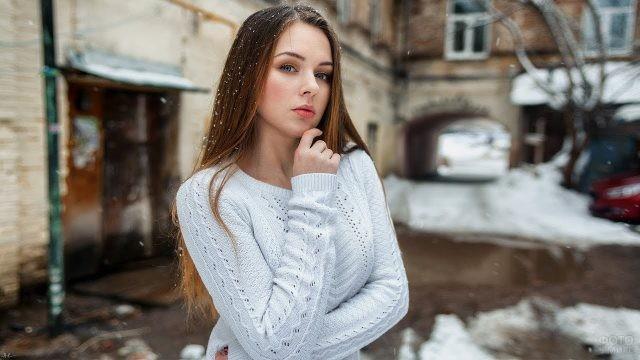 Девушка в свитере зимой в городском дворе