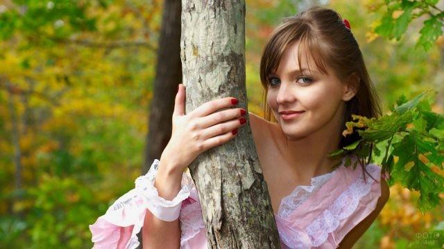 Девушка выглядывает из ствола дерева