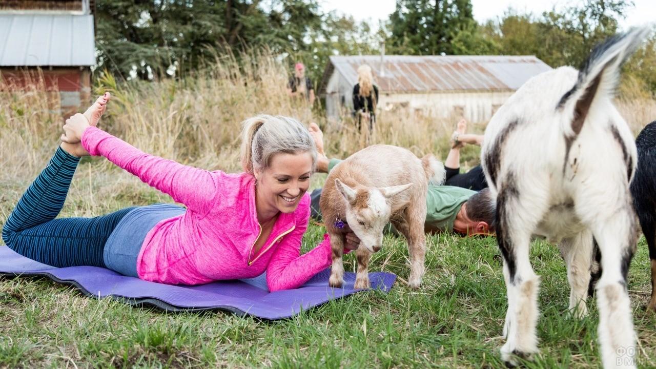 Девушка занимается йогой с козами