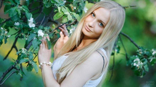 Голубоглазая блондинка у дерева