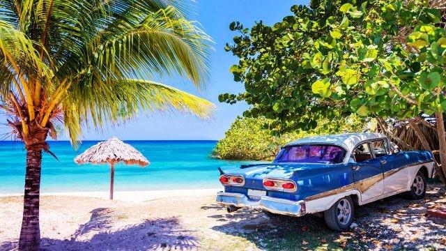 Ретро автомобиль припаркован в тени тропического пляжа