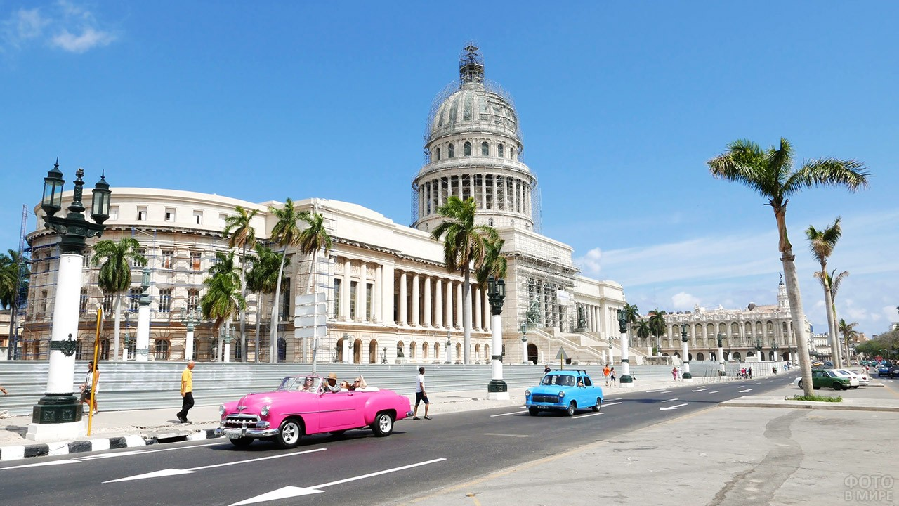 Туристы в розовом кабриолете в центре Гаваны