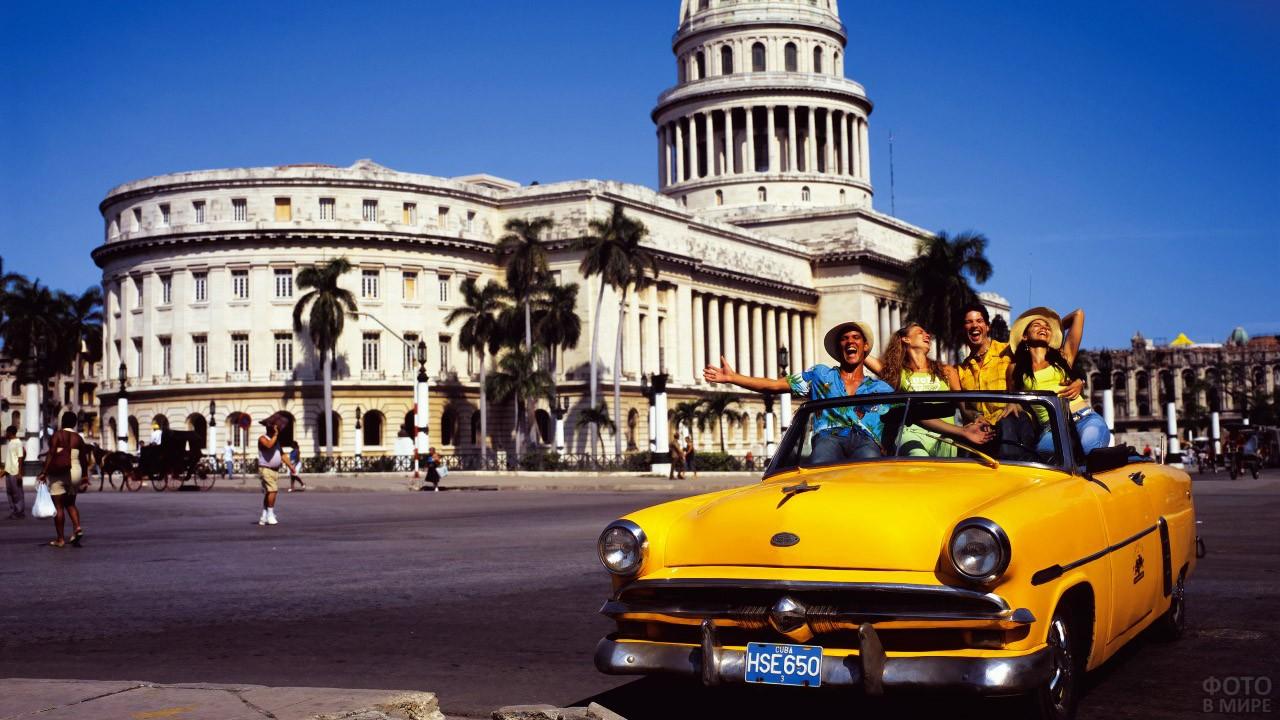 Туристы в жёлтом кабриолете у Капитолия в Гаване