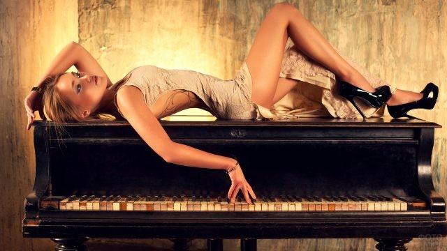 Блондинка лежит на пианино