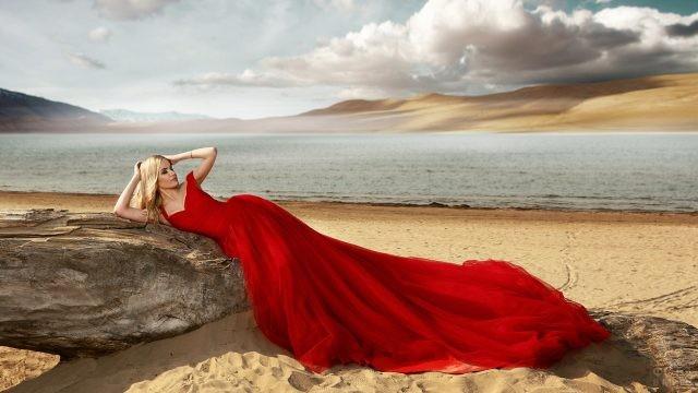 Блондинка в красном платье на пляже