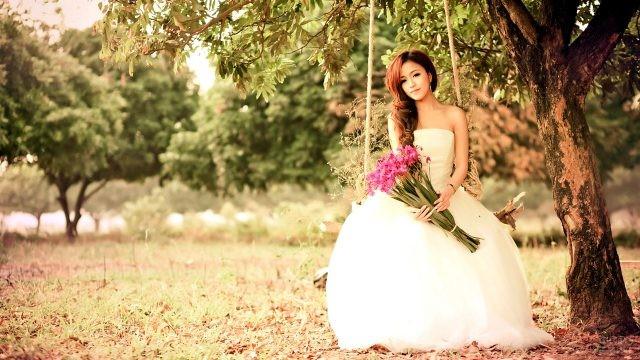 Девушка на качелях в свадебном платье