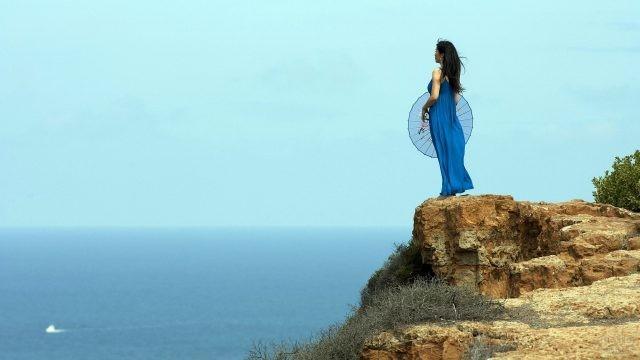 Девушка на скале у моря