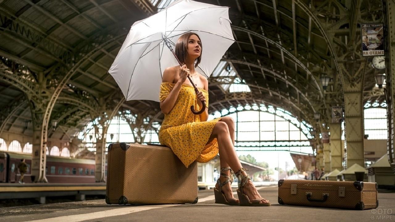 Девушка с зонтом сидит на чемодане