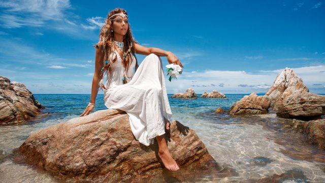 Девушка сидит на камне возле моря