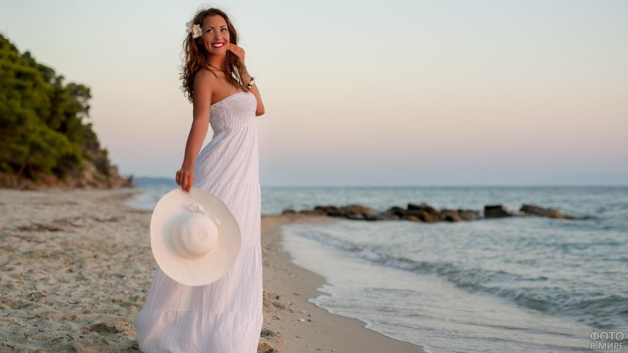 Девушка в белом платье держит шляпу