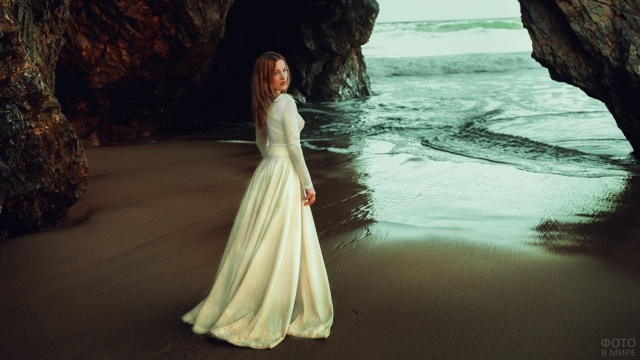Девушка в белом платье возле скал у моря