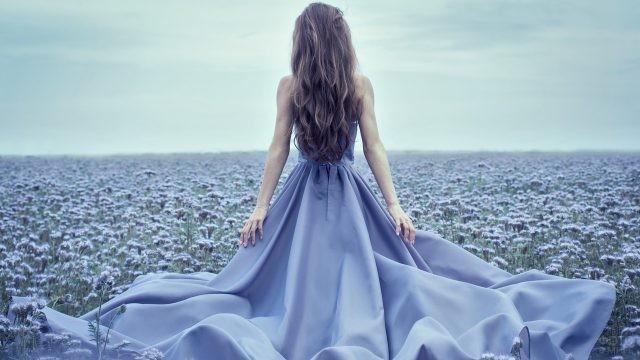 Девушка в синем платье среди цветов