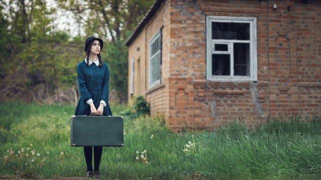 Девушка в зелёном платье держит чемодан