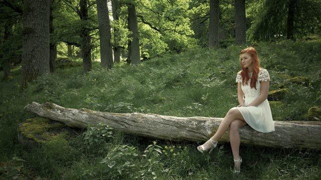 Рыжая девушка сидит на бревне