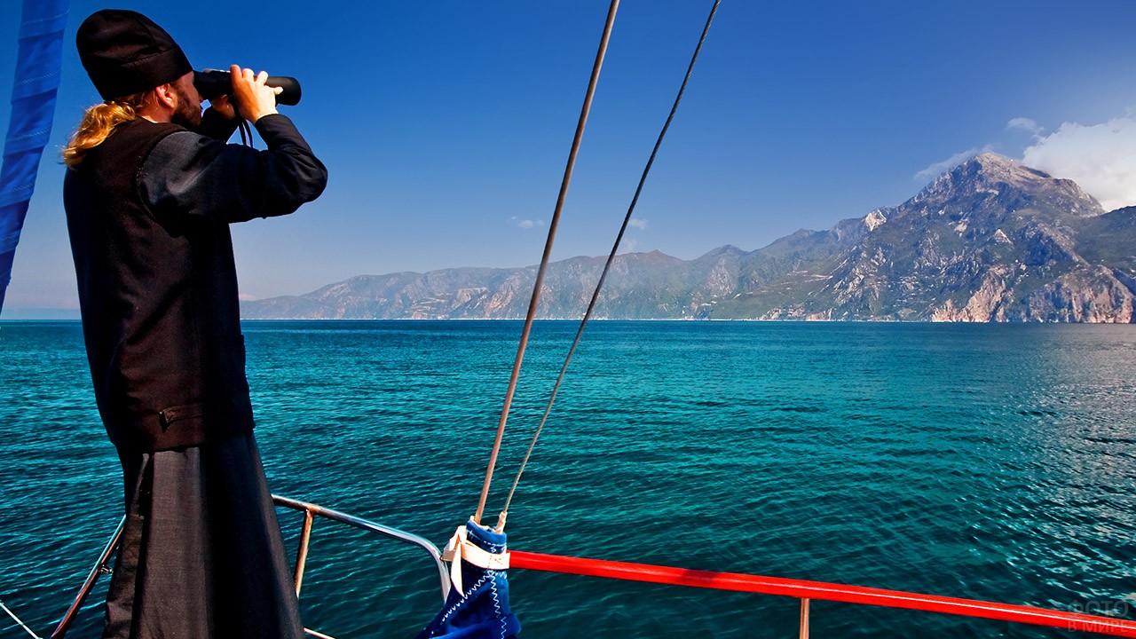 Монах смотрит в бинокль на Святую Гору с палубы корабля
