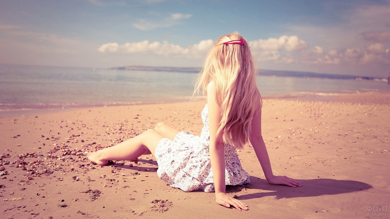 Блондинка сидит на пляже