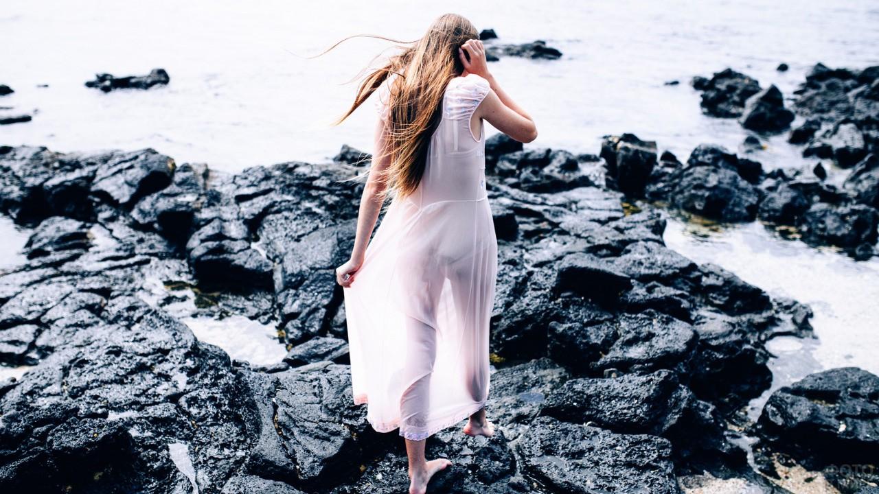Девушка идёт по камням