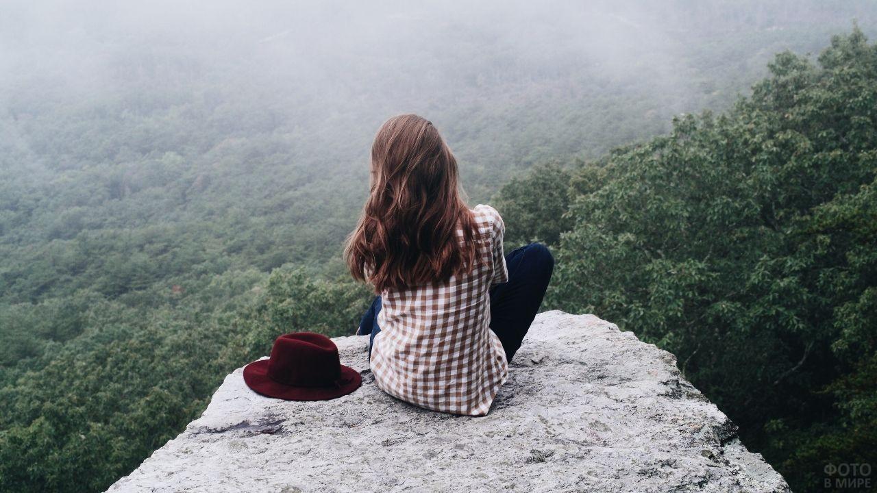 Девушка сидит на горе