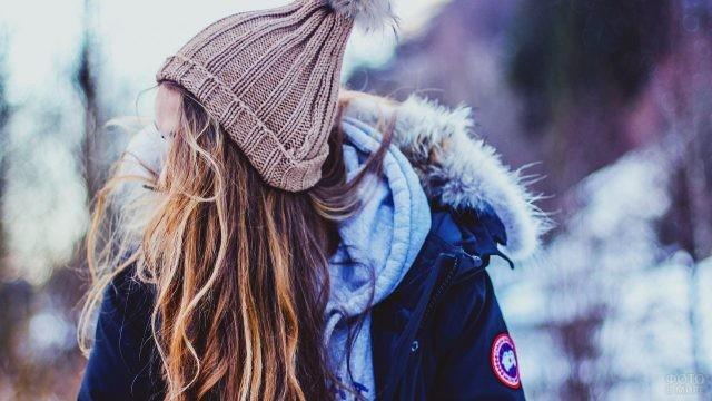 Девушка в куртке и вязаной шапке
