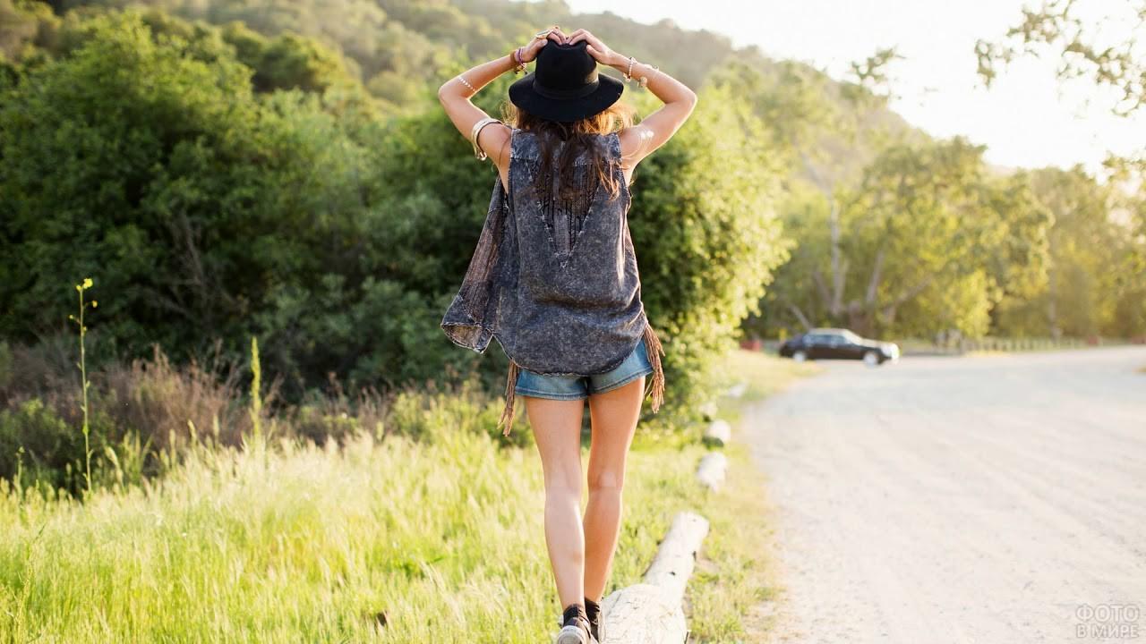 Девушка в шляпе идёт по дороге