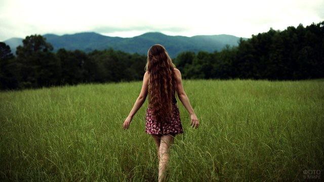 Длинноволосая девушка идёт по полю