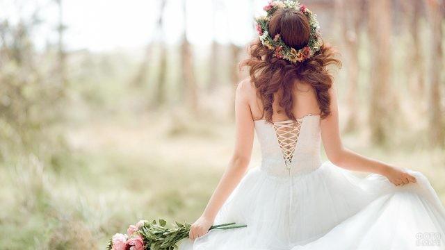 Невеста в белом платье с венком на голове