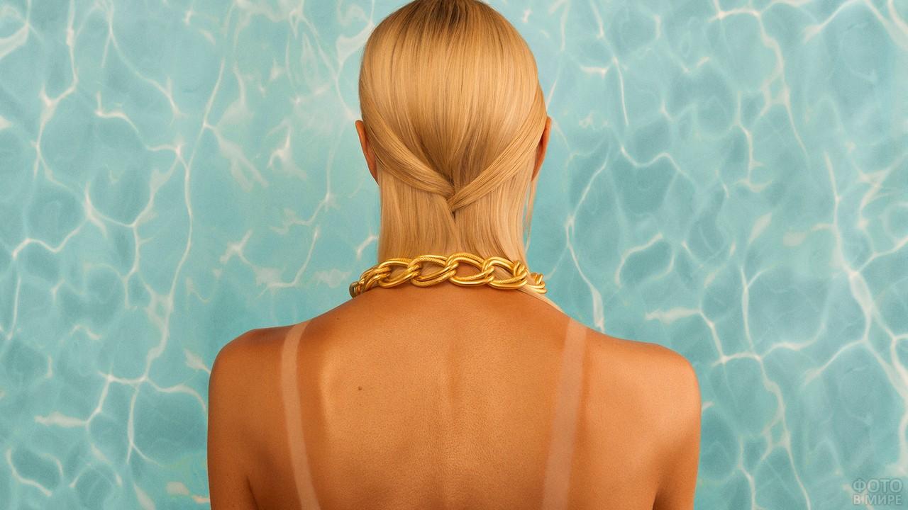 Светловолосая девушка стоит лицом к бассейну
