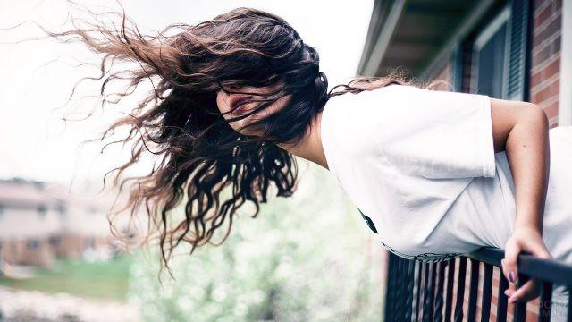 Ветер развивает волосы у девушки