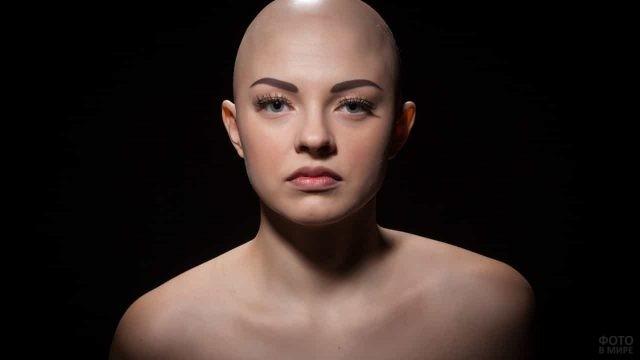 Девушка без волос на чёрном фоне