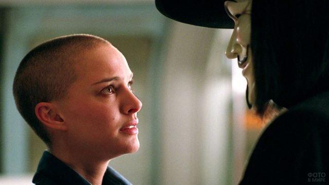 Девушка смотрит на человека в маске