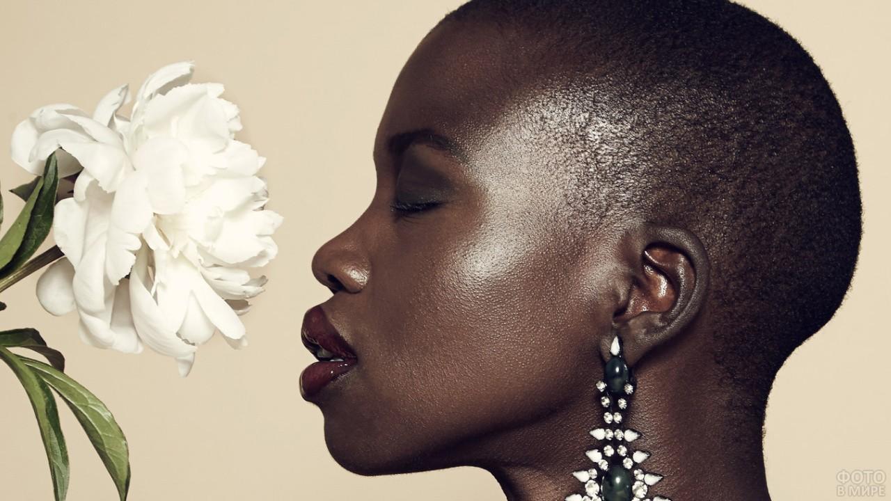 Темнокожая девушка нюхает цветок