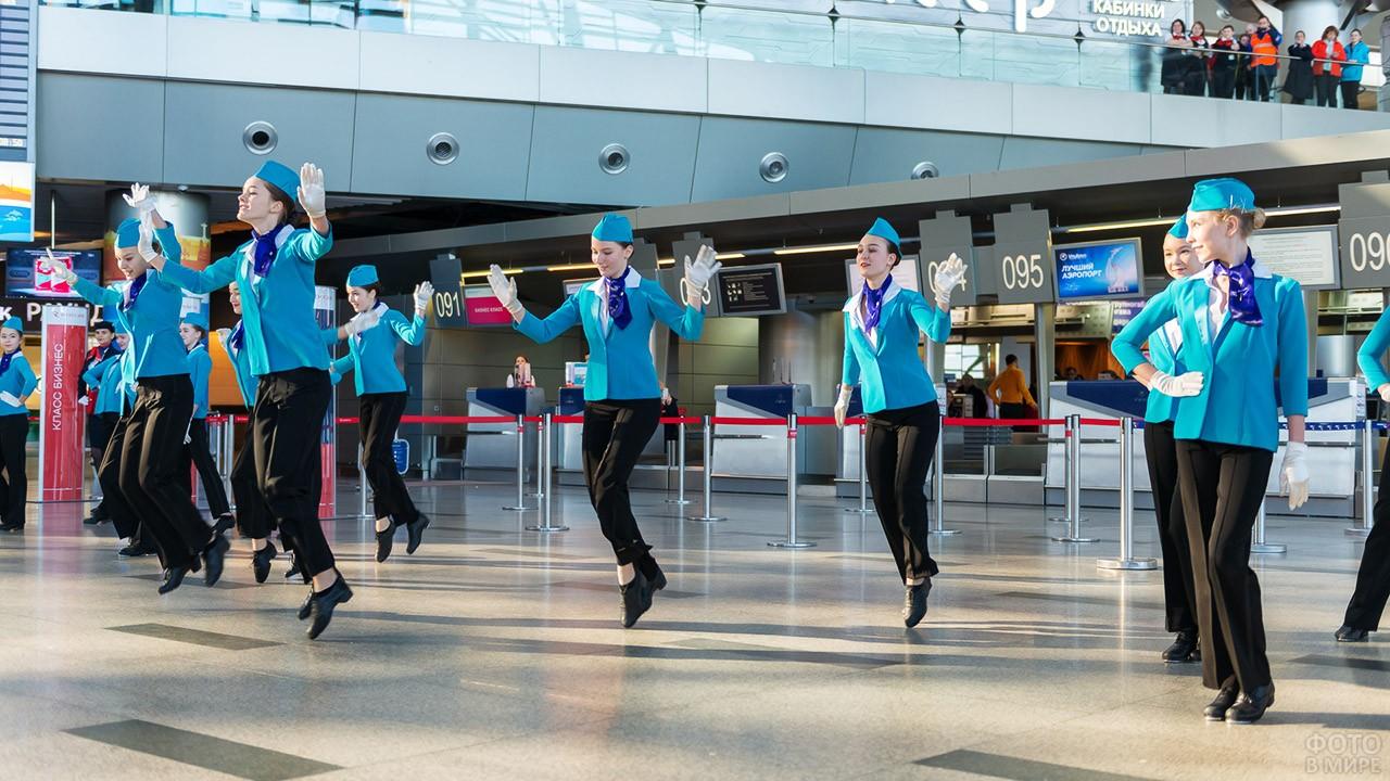 Танцовщицы в костюмах стюардесс выступают в зоне регистрации пассажиров