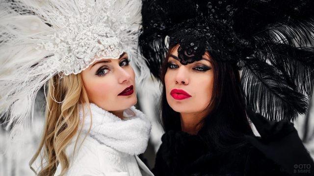 Блондинка и брюнетка в королевских головных уборах с перьями