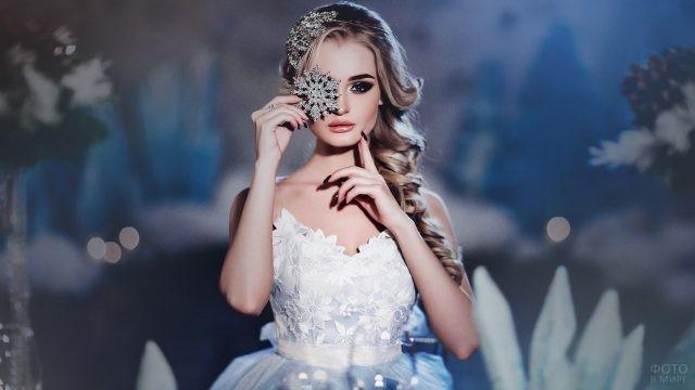 Блондинка в белом платье держит снежинку у лица