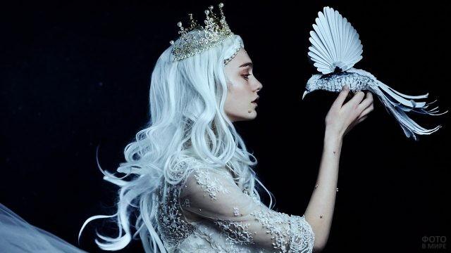 Блондинка в золотой короне держит в руках птицу