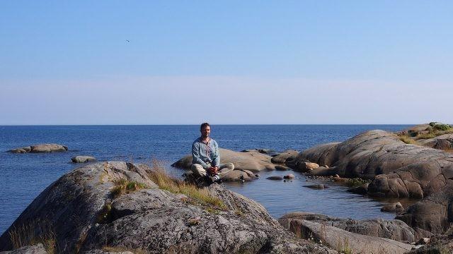 Турист медитирует в Северной Карелии на берегу моря