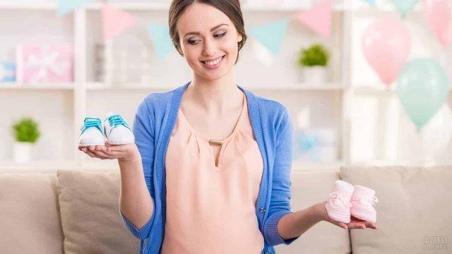Пинетки на руках беременной девушки