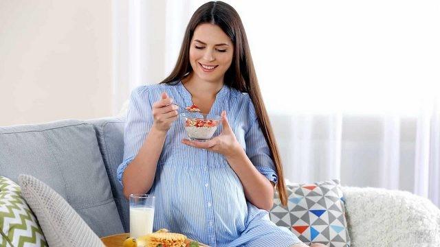 Завтрак беременной девушки на диване